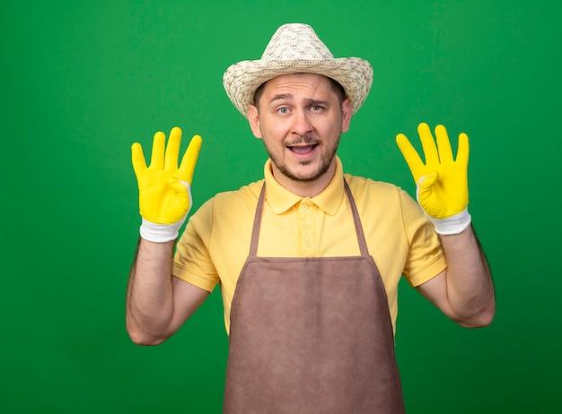 Junger gärtner, der overall und hut in arbeitshandschuhen trägt, zeigt und zeigt mit den fingern nummer acht, die fröhlich über grüner wand stehend lächeln Kostenlose Fotos