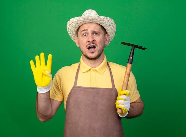 Junger gärtner, der overall und hut in den arbeitshandschuhen trägt, die mini-rechen halten, der front verwirrt betrachtet, zeigt nummer vier, die über grüner wand steht Kostenlose Fotos