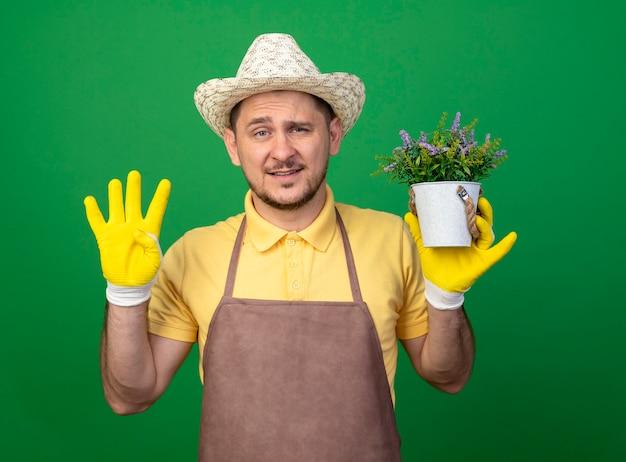 Junger gärtner, der overall und hut in den arbeitshandschuhen trägt, die topfpflanze betrachten, die front zeigt, die nummer vier steht über grüner wand Kostenlose Fotos
