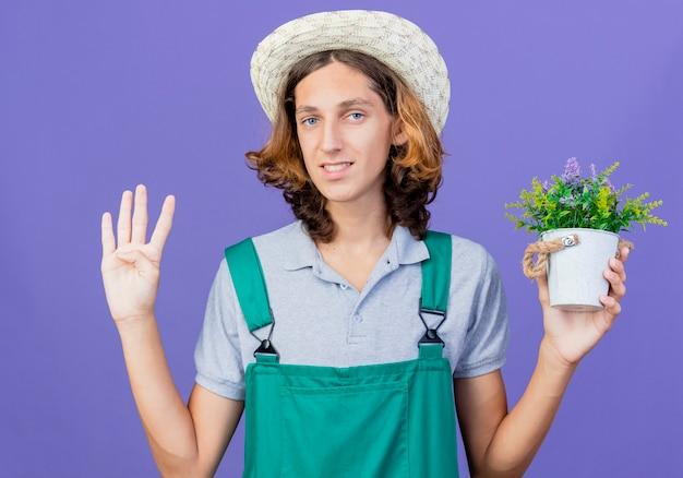 Junger gärtnermann, der overall und hut hält topfpflanze mit lächeln hält Kostenlose Fotos