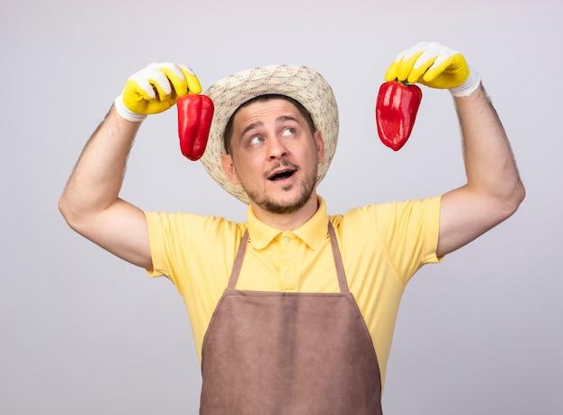 Junger gärtnermann, der overall und hut in arbeitshandschuhen hält, die rote paprika halten, die fröhlich lächeln Kostenlose Fotos