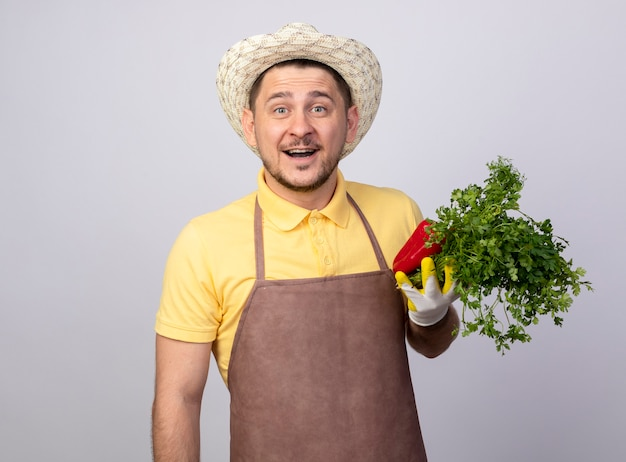 Junger gärtnermann, der overall und hut in arbeitshandschuhen trägt, die rote paprika und frische kräuter lächelnd lächelnd halten Kostenlose Fotos
