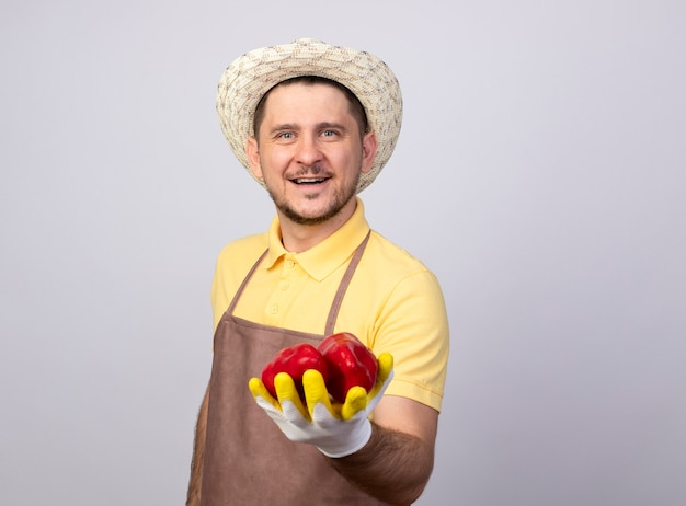 Junger gärtnermann, der overall und hut in arbeitshandschuhen trägt, die rote paprika zeigen, die mit glücklichem gesicht lächeln Kostenlose Fotos