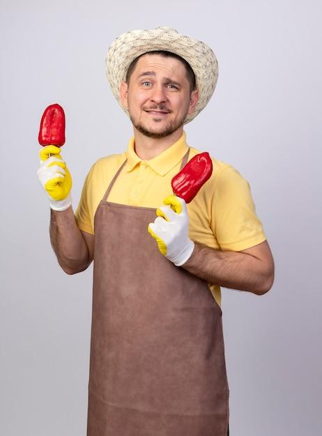 Junger gärtnermann, der overall und hut in den arbeitshandschuhen hält, die rote paprika halten, lächelnd mit glücklichem gesicht, das über weißer wand steht Kostenlose Fotos