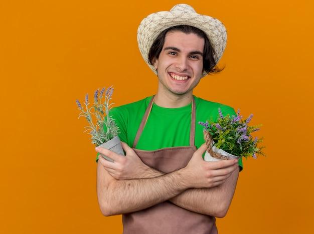 Junger gärtnermann in der schürze und im hut, die topfpflanzen halten, die fröhlich lächelnd mit gekreuzten händen über orange wand stehen Kostenlose Fotos