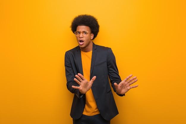 Junger geschäftsafroamerikanermann über einer orange wand etwas zurückweisend, eine geste des ekels tuend Premium Fotos