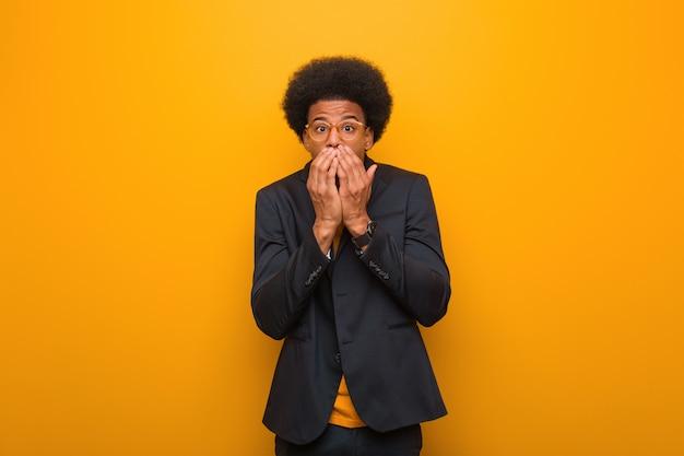 Junger geschäftsafroamerikanermann über einer orange wand sehr sca und ängstlich versteckt Premium Fotos