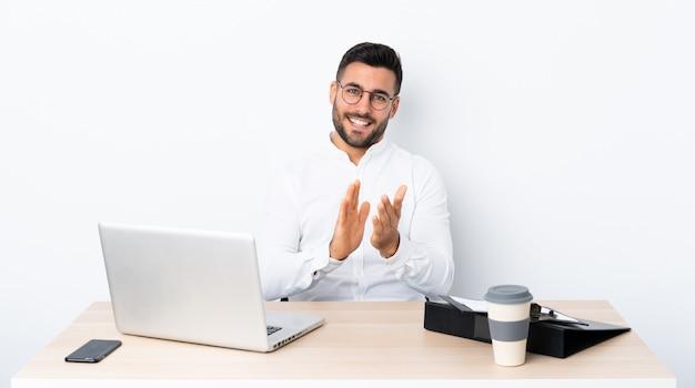 Junger geschäftsmann an einem arbeitsplatz applaudierend nach darstellung in einer konferenz Premium Fotos