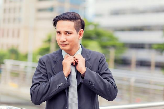 Junger geschäftsmann asiens vor dem modernen gebäude herein in die stadt Premium Fotos