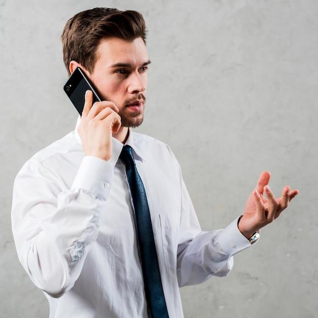 Junger geschäftsmann, der am intelligenten telefon gestikuliert steht gegen graue wand gestikuliert Kostenlose Fotos