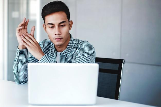 Junger geschäftsmann, der an computer-laptop im büro arbeitet. Premium Fotos