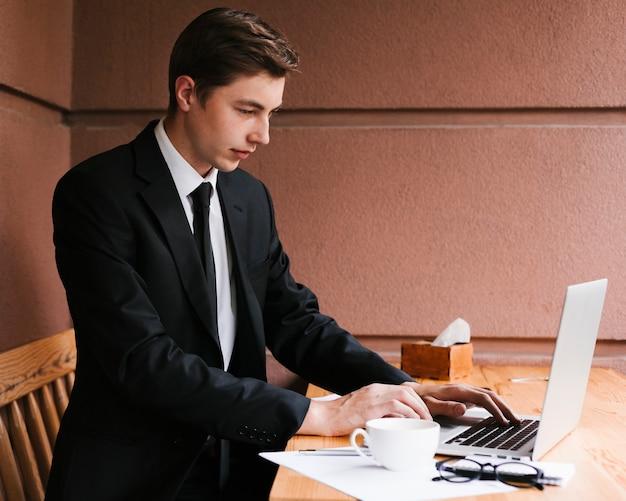 Junger geschäftsmann, der an laptop arbeitet Kostenlose Fotos