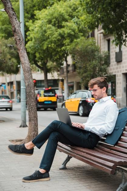Junger geschäftsmann, der auf bank über dem bürgersteig unter verwendung des laptops sitzt Kostenlose Fotos