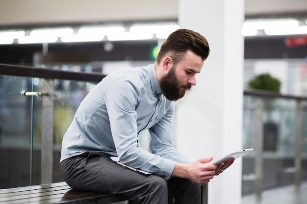 Junger geschäftsmann, der auf bank unter verwendung der digitalen tablette sitzt Kostenlose Fotos
