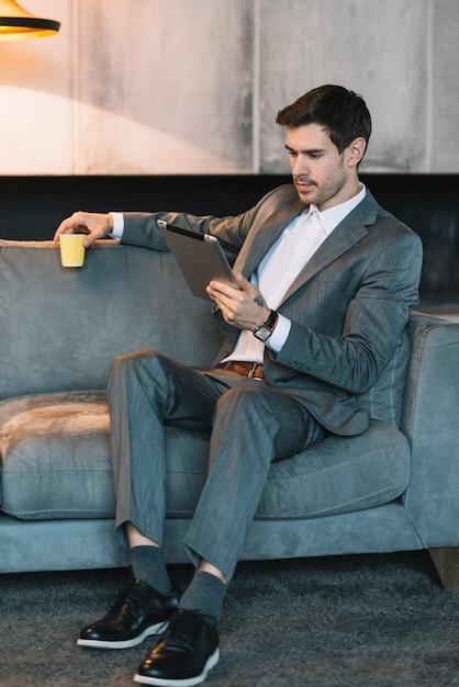 Junger geschäftsmann, der auf dem sofa hält die kaffeetasse betrachtet digitale tablette sitzt Kostenlose Fotos