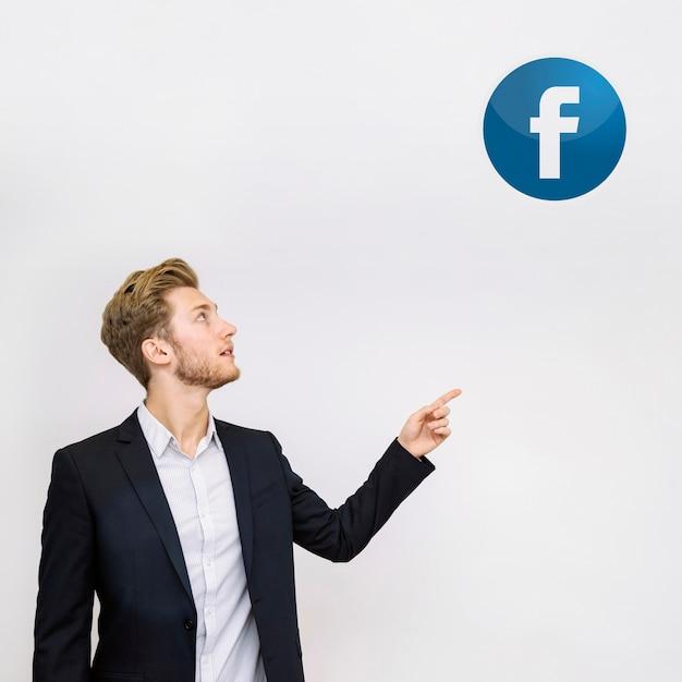 Junger geschäftsmann, der auf facebook-ikone auf wand zeigt Kostenlose Fotos