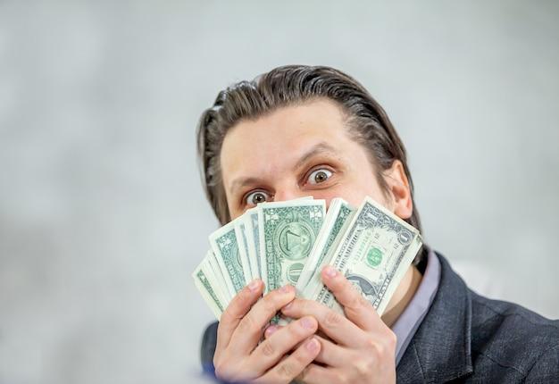 Junger geschäftsmann, der bargeld hält - das konzept von erfolg und freude Kostenlose Fotos