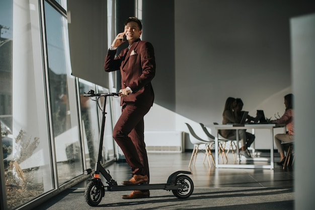 Junger geschäftsmann, der durch das bürofenster mit elektroroller steht und handy verwendet Premium Fotos