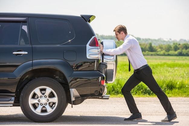 Junger geschäftsmann, der ein auto mit leerem kraftstofftank drückt. Premium Fotos