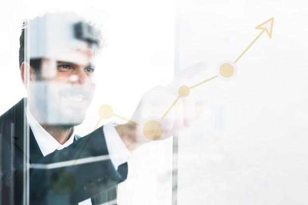 Junger geschäftsmann, der finger auf zunehmendes diagramm auf transparentem glas zeigt Kostenlose Fotos