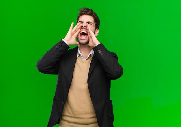 Junger geschäftsmann, der glücklich, aufgeregt und positiv sich fühlt, einen großen ruf heraus mit den händen nahe bei dem mund gebend und rufen auf grün aus Premium Fotos