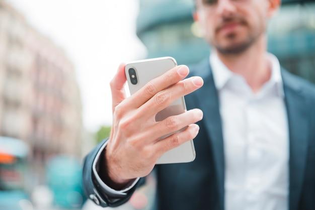 Junger geschäftsmann, der in der hand smartphone hält Kostenlose Fotos