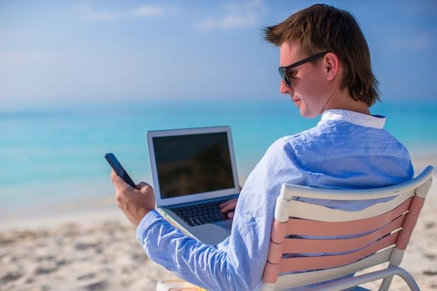 Junger geschäftsmann, der mit laptop auf tropischem strand arbeitet Premium Fotos