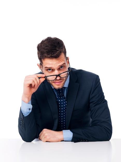 Junger geschäftsmann, der schwarze brille hält Kostenlose Fotos