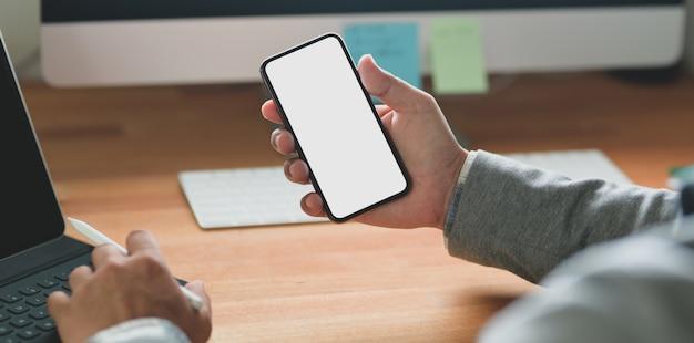 Junger geschäftsmann, der smartphone des leeren bildschirms beim arbeiten an seinem projekt hält Premium Fotos