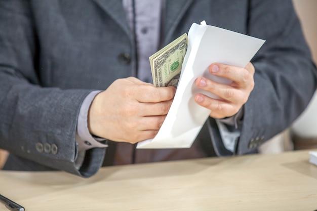 Junger geschäftsmann, der von seinem büro arbeitet und bargeld zählt Kostenlose Fotos