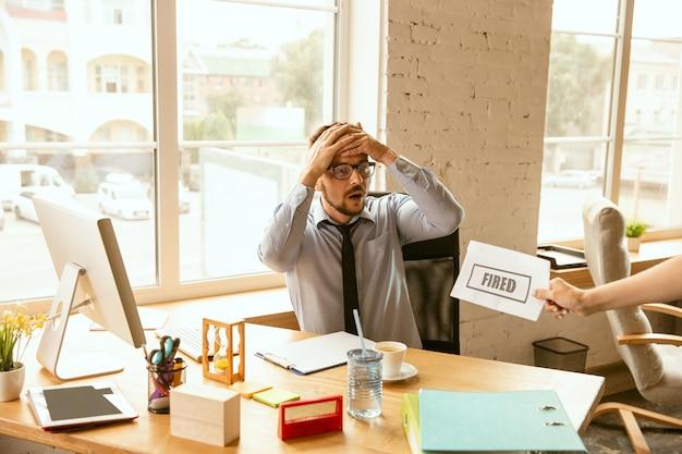 Junger geschäftsmann gefeuert, sieht verärgert aus. muss seine bürogegenstände packen und den arbeitsplatz für neue arbeiter verlassen. probleme in beruf, stress, arbeitslosigkeit, neuer lebensweise oder karriereende. Kostenlose Fotos