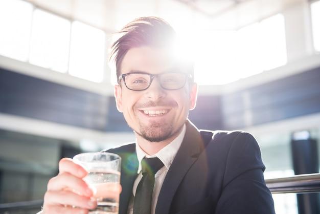 Junger geschäftsmann hält ein glas wasser. Premium Fotos