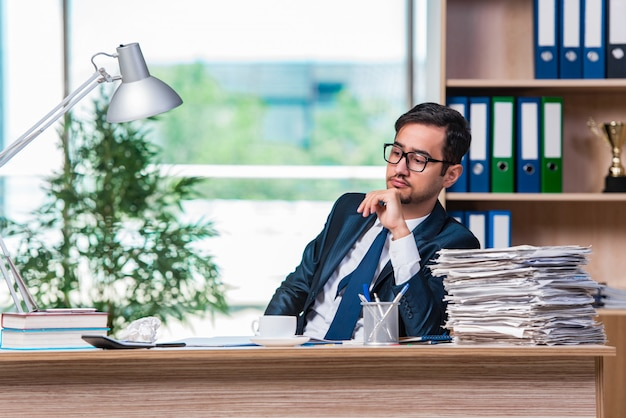Junger geschäftsmann im stress mit viel papierkram Premium Fotos