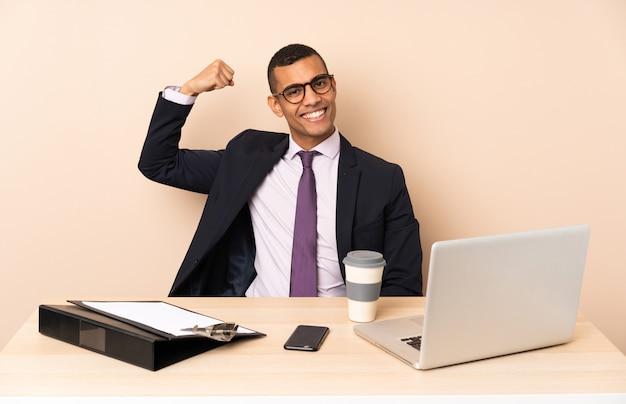 Junger geschäftsmann in seinem büro mit einem laptop und anderen dokumenten, die starke geste tun Premium Fotos