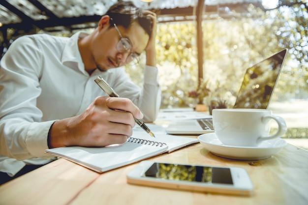 Junger geschäftsmann ist, notizbuch mit druck zu schreiben. Premium Fotos