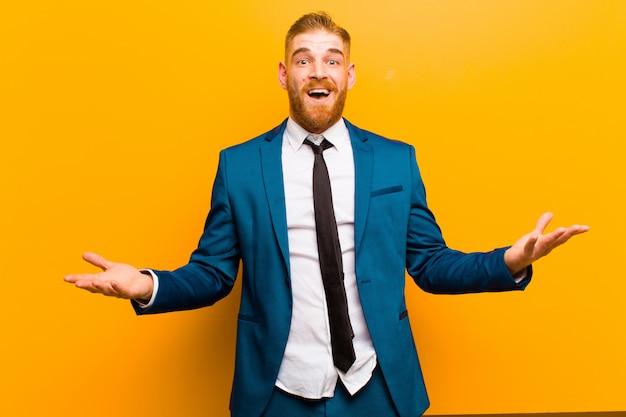 Junger geschäftsmann mit rotem kopf, offenem mund und erstaunt, geschockt und erstaunt über eine unglaubliche überraschung gegen orange Premium Fotos