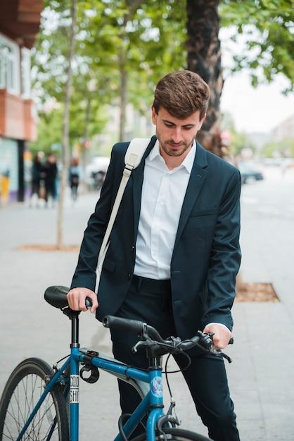 Junger geschäftsmann mit seinem rucksack, der mit fahrrad auf straße steht Kostenlose Fotos