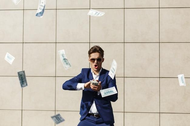 Junger geschäftsmann throughs um dollar und tänze auf der straße Kostenlose Fotos