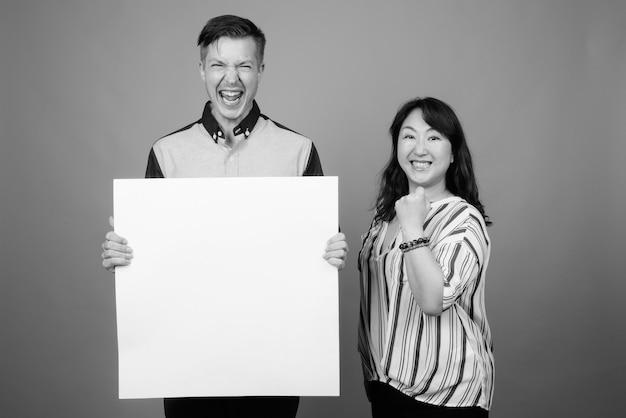 Junger geschäftsmann und reife japanische geschäftsfrau zusammen gegen grau in schwarzweiss Premium Fotos