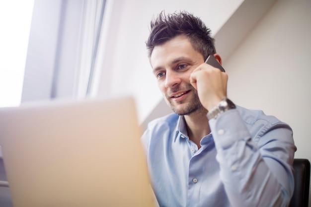 Junger geschäftsmann unter verwendung des handys und arbeiten an laptop Premium Fotos