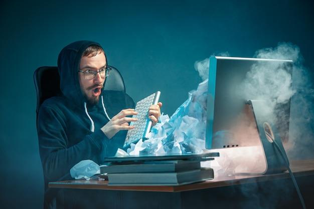 Junger gestresster gutaussehender geschäftsmann, der am schreibtisch im modernen büro arbeitet und laptop-bildschirm schreit und über spam wütend ist Kostenlose Fotos