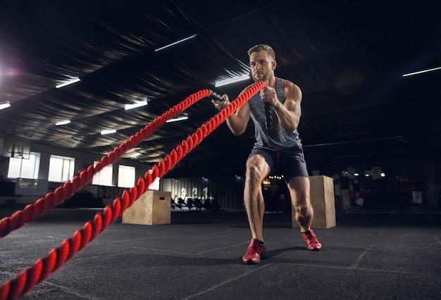 Junger gesunder mann, athlet, der übung mit den seilen im fitnessstudio tut. ein einzelnes männliches model übt hart und trainiert seinen oberkörper. konzept des gesunden lebensstils, des sports, der fitness, des bodybuildings, des wohlbefindens. Kostenlose Fotos