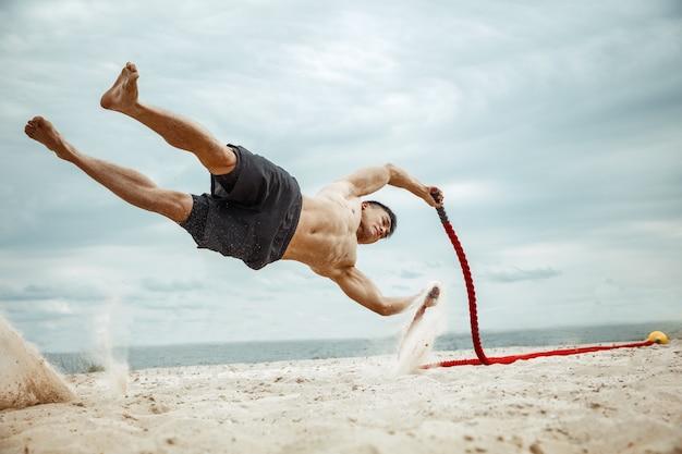 Junger gesunder mannathlet, der kniebeugen am strand tut Kostenlose Fotos