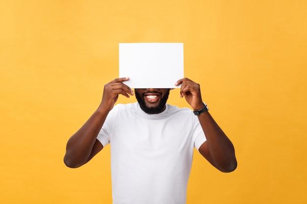 Junger glücklicher afroamerikaner, der hinter einem leeren papier, getrennt auf gelbem hintergrund sich versteckt Premium Fotos