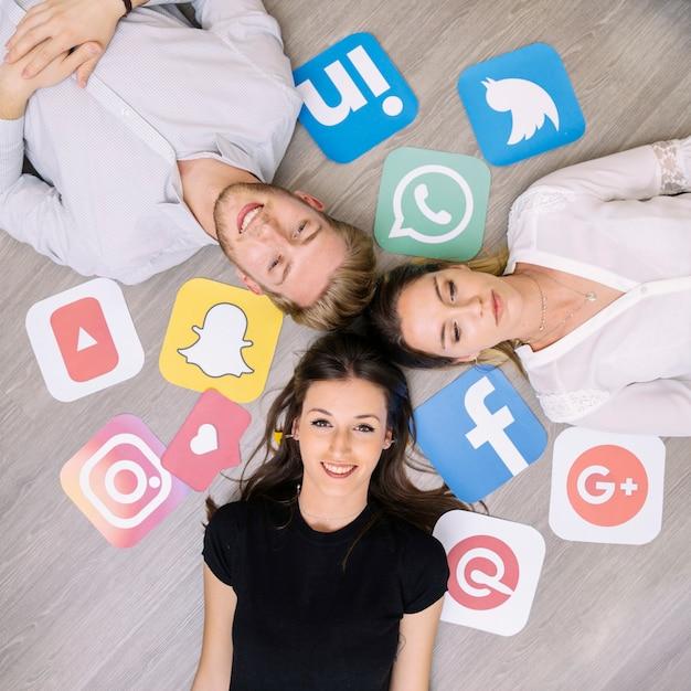 Junger glücklicher freund, der auf boden mit social media-logos liegt Kostenlose Fotos