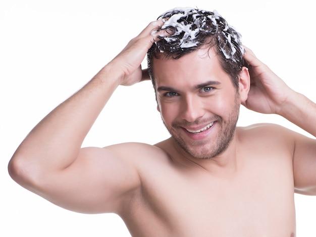 Junger glücklicher lächelnder mann, der haare mit shampoo wäscht - lokalisiert auf weiß. Kostenlose Fotos