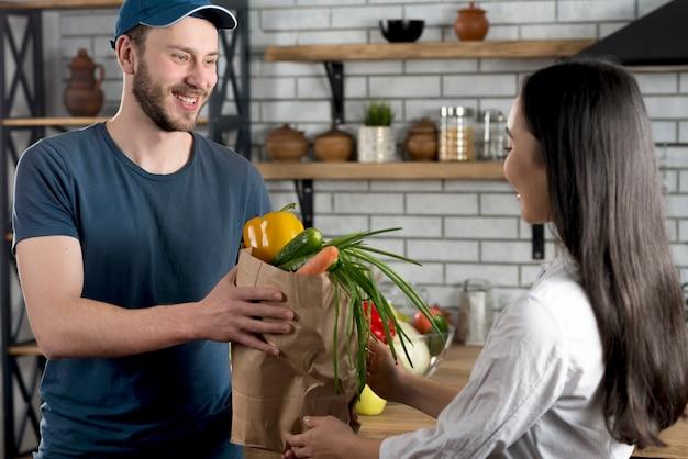 Junger glücklicher lieferer, der zu hause der frau in der küche lebensmittelgeschäft gibt Kostenlose Fotos