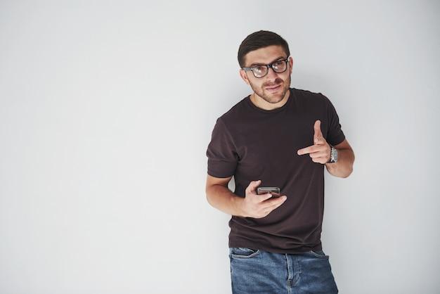 Junger glücklicher mann lässig gekleidet mit smartphone auf weiß Kostenlose Fotos