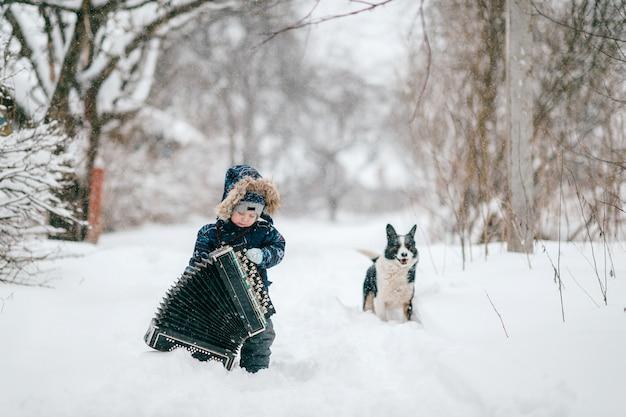 Junger glücklicher musiker. komischer junge, der großes schweres akkordeon hält. tragendes musikerinstrument des reizenden lustigen männlichen kindes auf der straße des verschneiten winters im freien. Premium Fotos