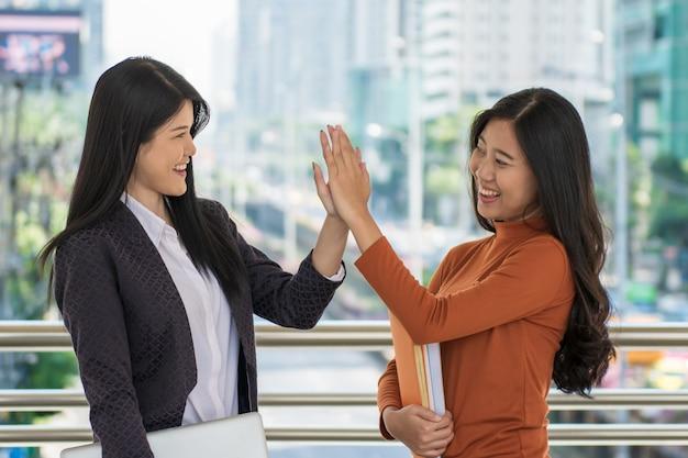 Junger glücklicher student, der bücher und klapshände oder hallo fünf am campus zusammenhält. Premium Fotos